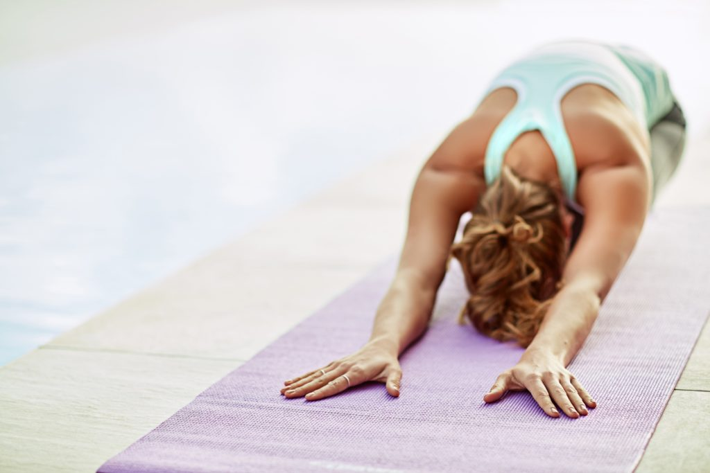 A woman on a yoga mat doing the downward dog yoga pose