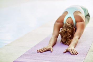A woman on a yoga mat doing the downward dog yoga pose