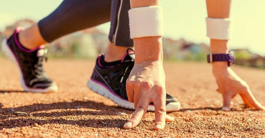 A runner with their hands on the floor getting ready to start a sprint
