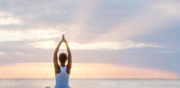A woman practicing yoga at the seashore