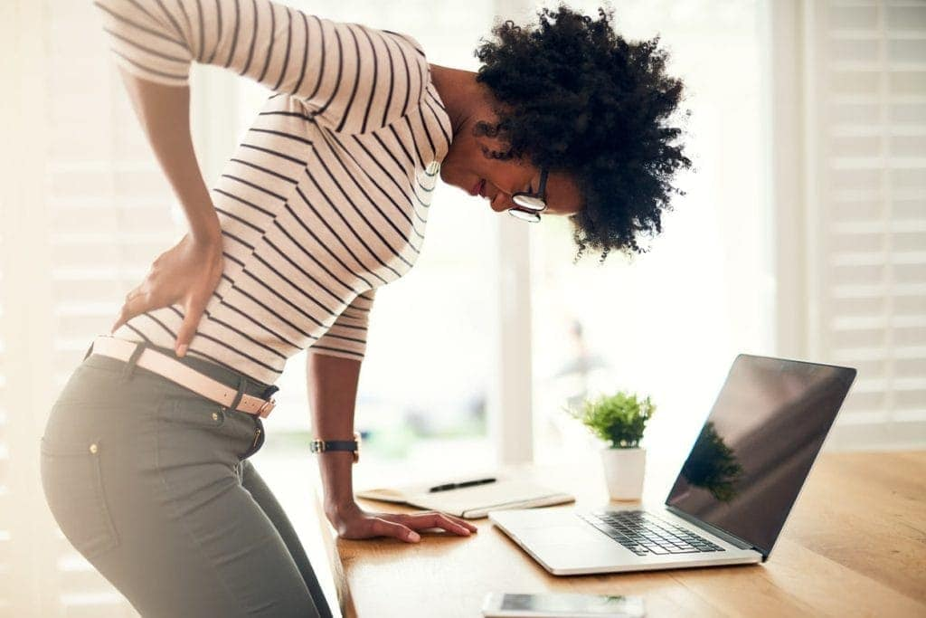 A woman leaning over her desk as she struggles with back pain