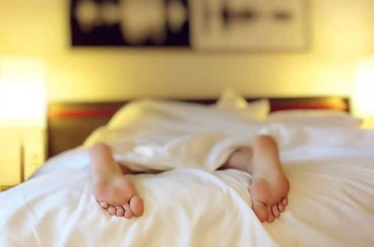 Close up of a person lying under the covers in bed