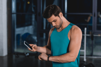 A man checking the progress of his fitness tracker on his mobile phone