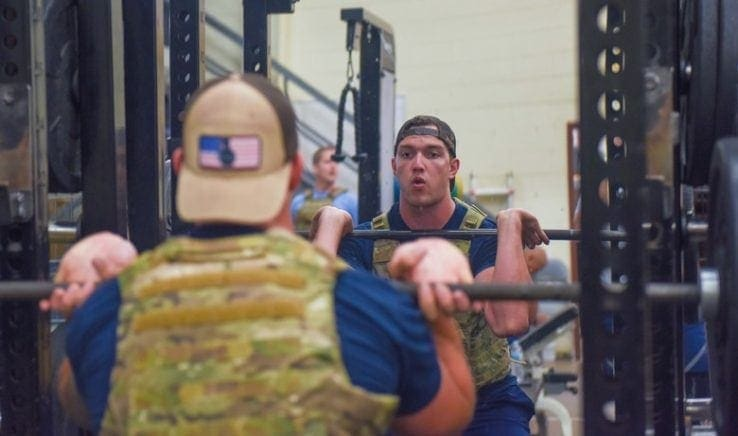 A man lifting weights while wearing a weighted vest