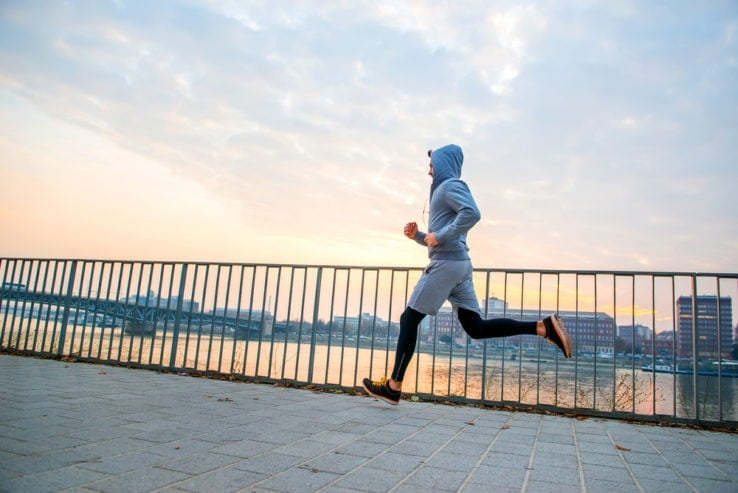 A man running by the water during sunrise