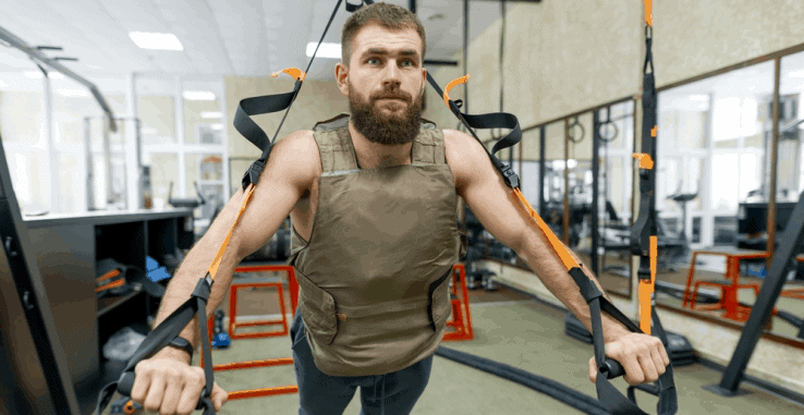 A man wearing a weight vest while using a TRX machine in the gym