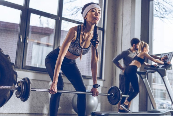 A woman exercising with a full length barbell