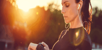 A woman getting ready to go jogging as the sun rises