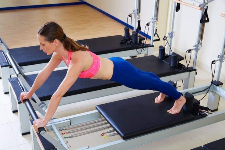 A woman stretched out on a reformer pilates machine