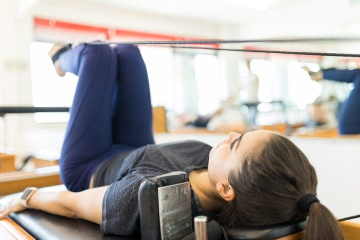 A woman using a pilates reformer machine in the gym
