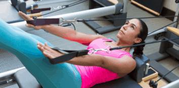 A woman using a reformer pilates machine