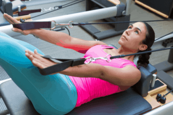 A woman using a reformer pilates machine