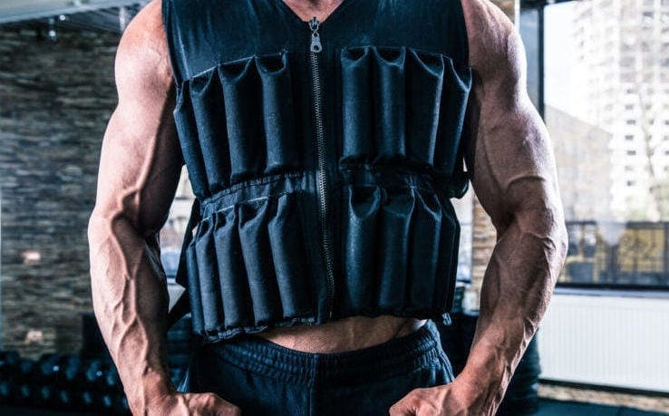 Close up of a man wearing a black weighted vest
