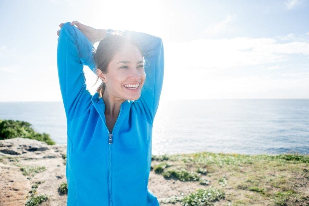 A woman smiling while stretching out her arms and back