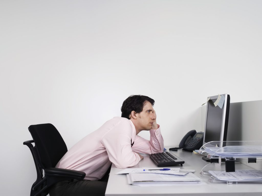 A man slouching at his office desk