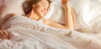 A women smiling as she lies in bed as the sun rises
