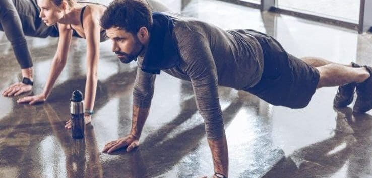 Multiple people doing push ups while wearing fitness trackers