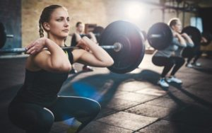A woman doing squats with a long barbell in the gym