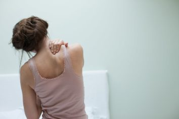 A woman massaging her own neck and back