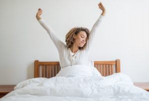A woman yawning in bed as she wakes up