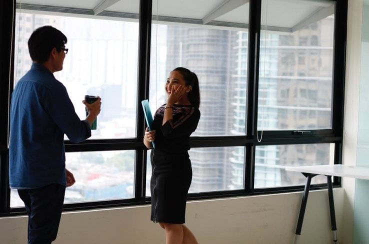 A woman and a man having a conversation in an office
