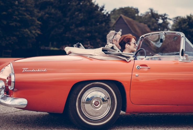 An elderly couple driving in their orange classic car