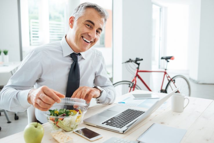 A business man in his office eating a salad