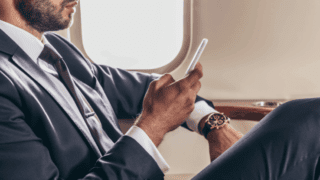 A business man using his phone while sat on a plane