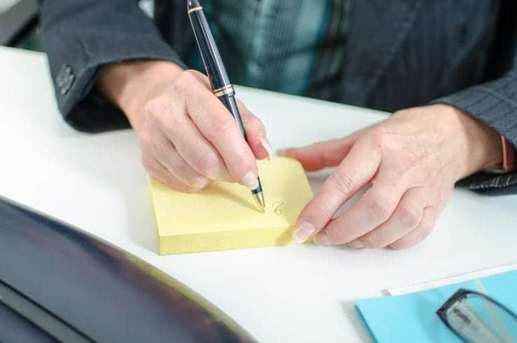A business woman writing out a post it note