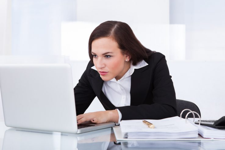 A businesswoman slouching over her desk