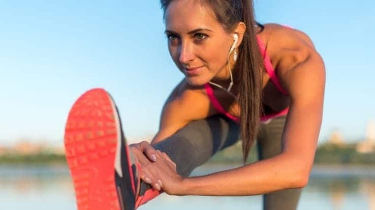 A close up of a female runner stretching out her hamstrings