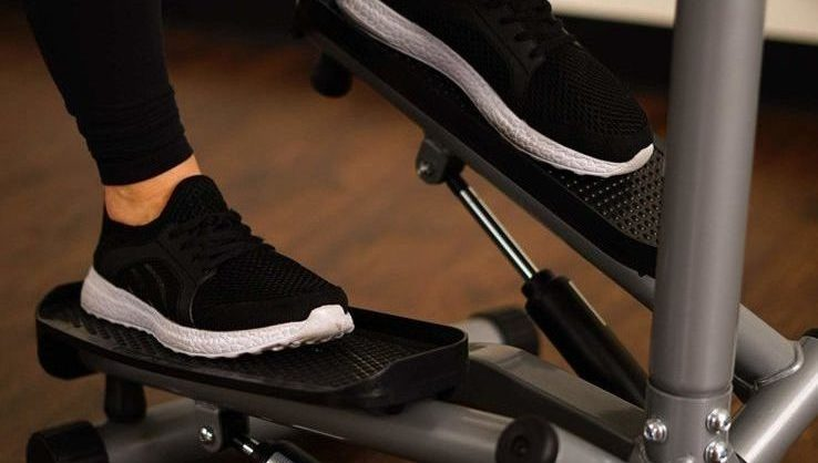 A close up of a woman using her stair stepper machine