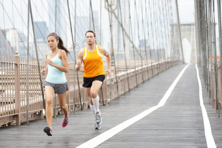 A couple running together over a bridge