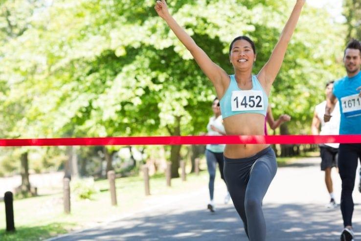 A female runner celebrating as she crosses the finish line of a race