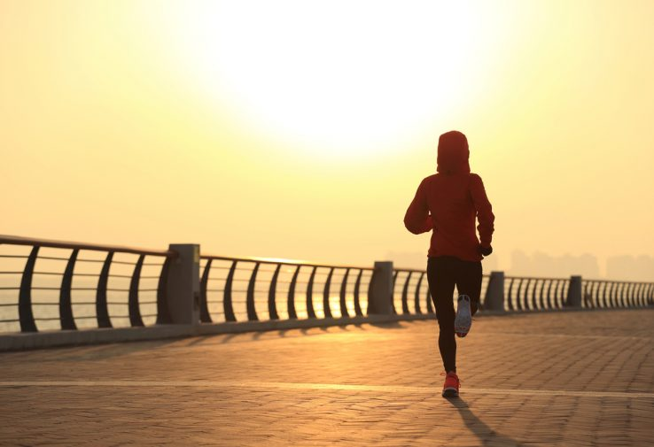 A female runner running down the pier as the sun rises
