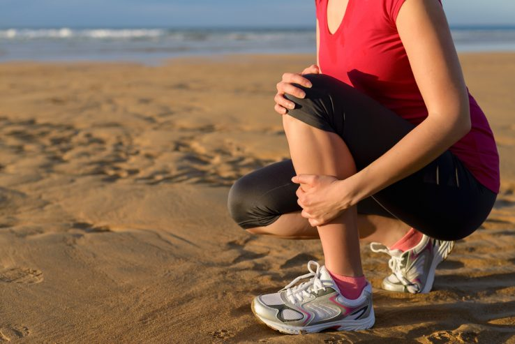 A female running suffering with a shin injury
