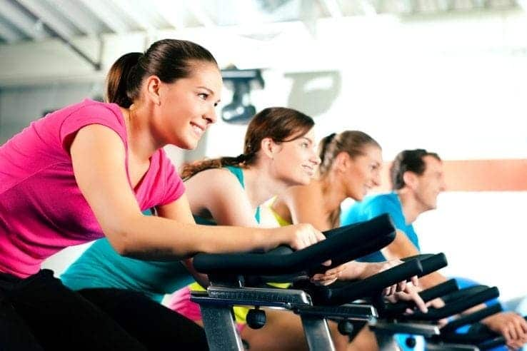 A group of women all exercising together on exercise bikes