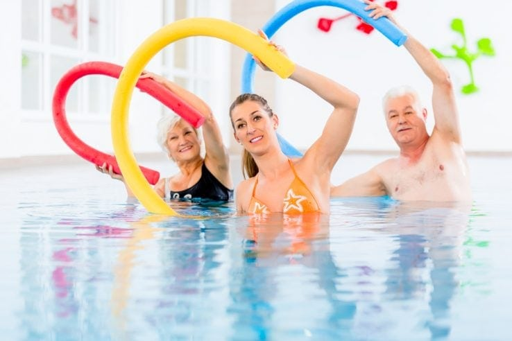 A lady teaching an elderly couple in a aqua therapy class
