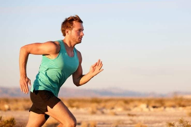 A male runner running through the desert
