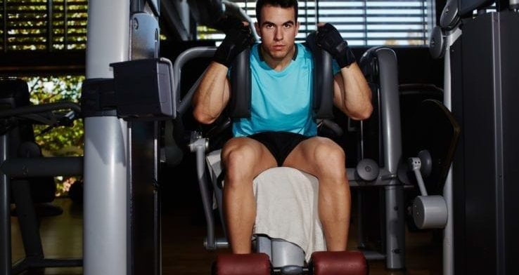 A man about to use a ab crunch machine in the gym