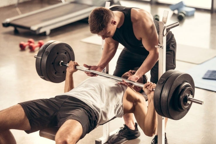 A man benchpressing while his friend helps spot him