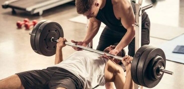 A man bench pressing while his friend helps spot him