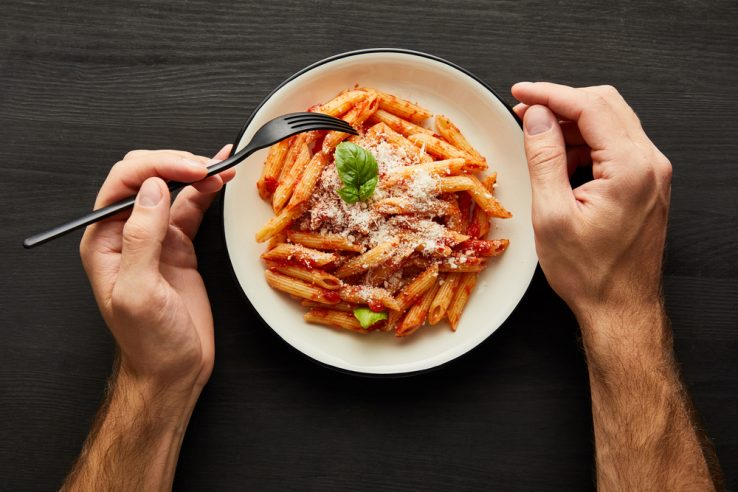 A man getting ready to eat a bowl of pasta