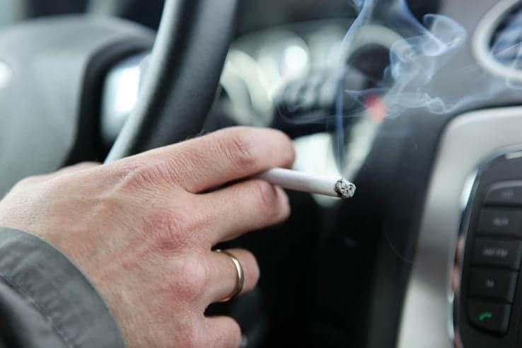 A man in his car smoking