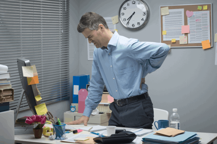 A man in his office having problems with his lower back