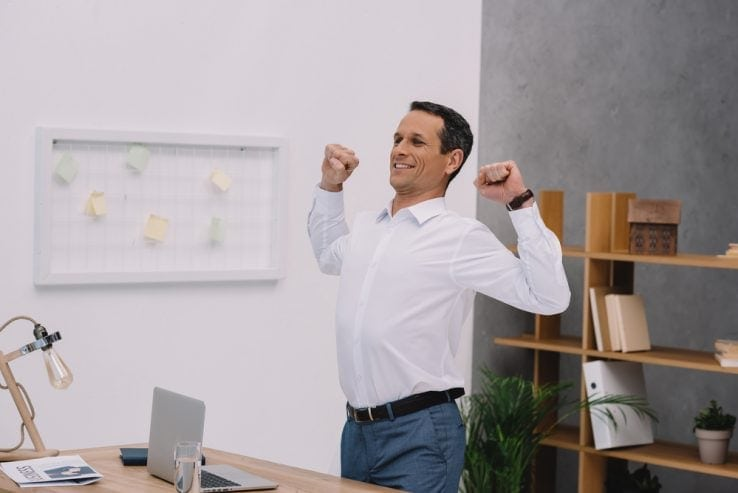 A man in his office stood up and stretching
