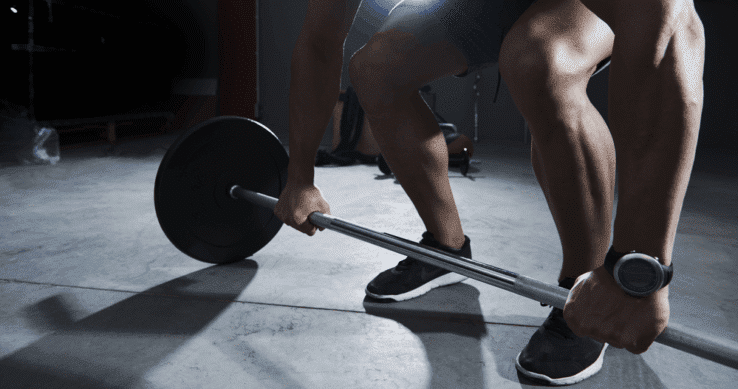 A man in the gym about to lift a barbell weight