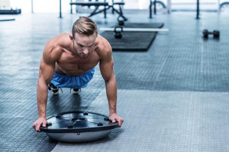 A man in the gym doing core exercises with a balance board