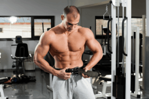 A man in the gym wearing a weight lifting belt