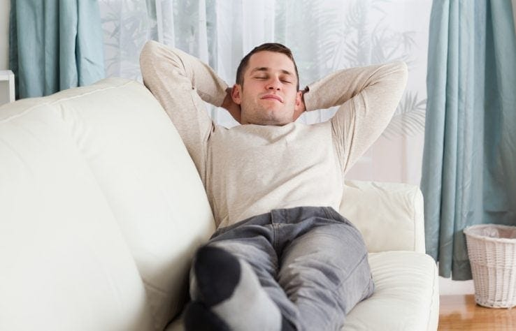 A man lay down on the sofa resting his legs